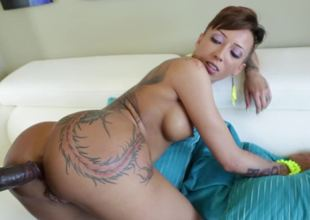 A slut that has hot tattoos is riding a large black shlong on the sofa
