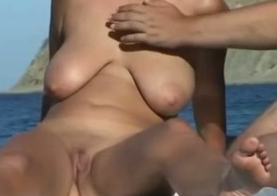 My well-endowed blonde wife enjoys sucking my wang on a beach