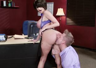 A breasty milf with large silicone filled udders is fucked in the office