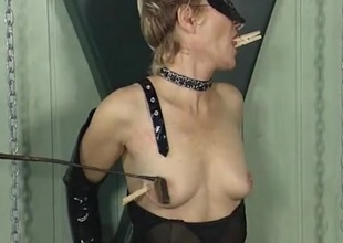 Clothes pins upstairs the tits of a girl in black latex