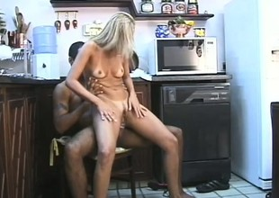 In the kitchen, a horny blonde housewife gets fucked hard all round both holes