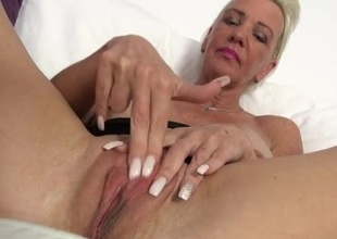 Granny with big fake tits fingers her pussy